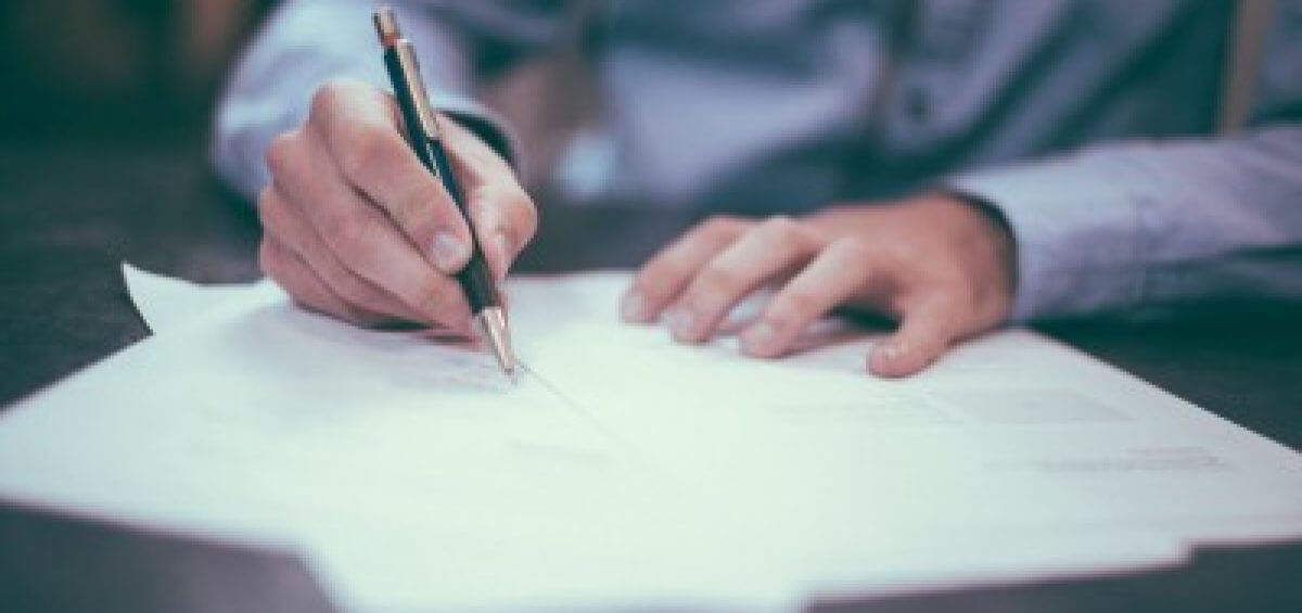 Man signing through business documents