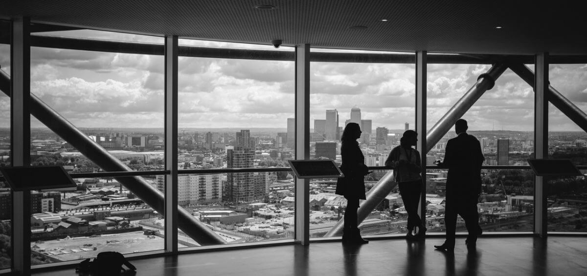 Black and white image of people viewing the city inside of large building