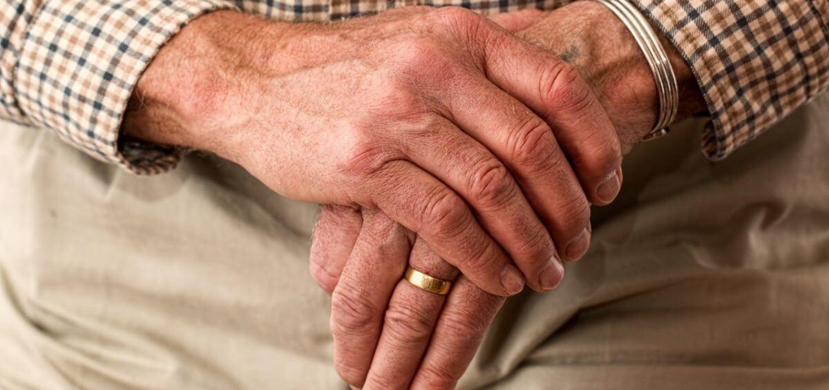 Elderly older mans hands on top of his walking stick