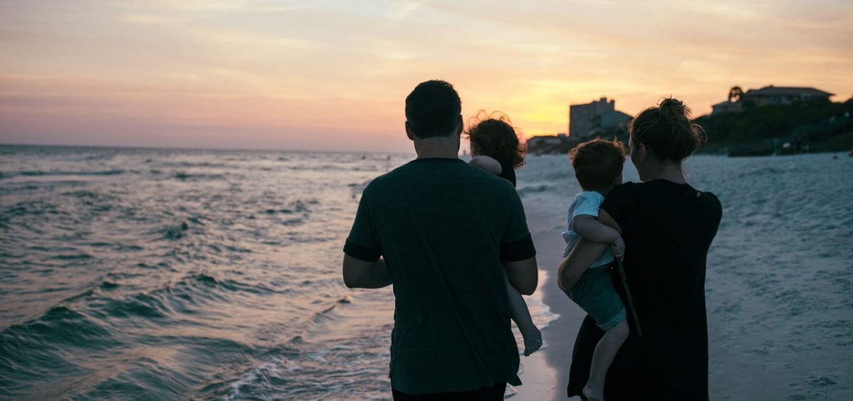 Young family walking on the shore of the beach with beautiful sunset