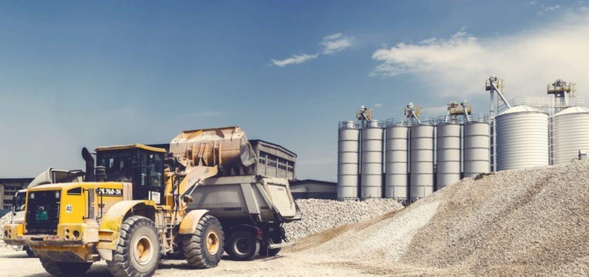 Yellow heavy equipment truck working on site with Schmitz truck
