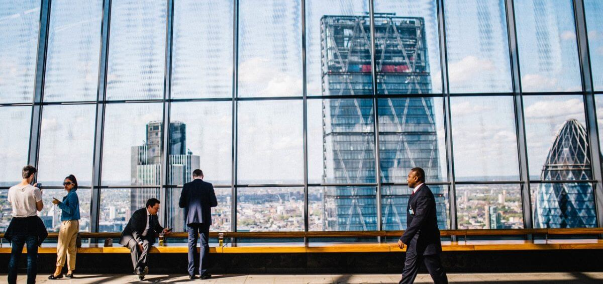 A businessman walking through a skyscraper building with view of city