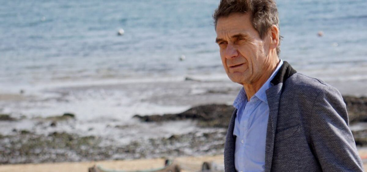 An older man looking pensive as he stands on the beach's shore