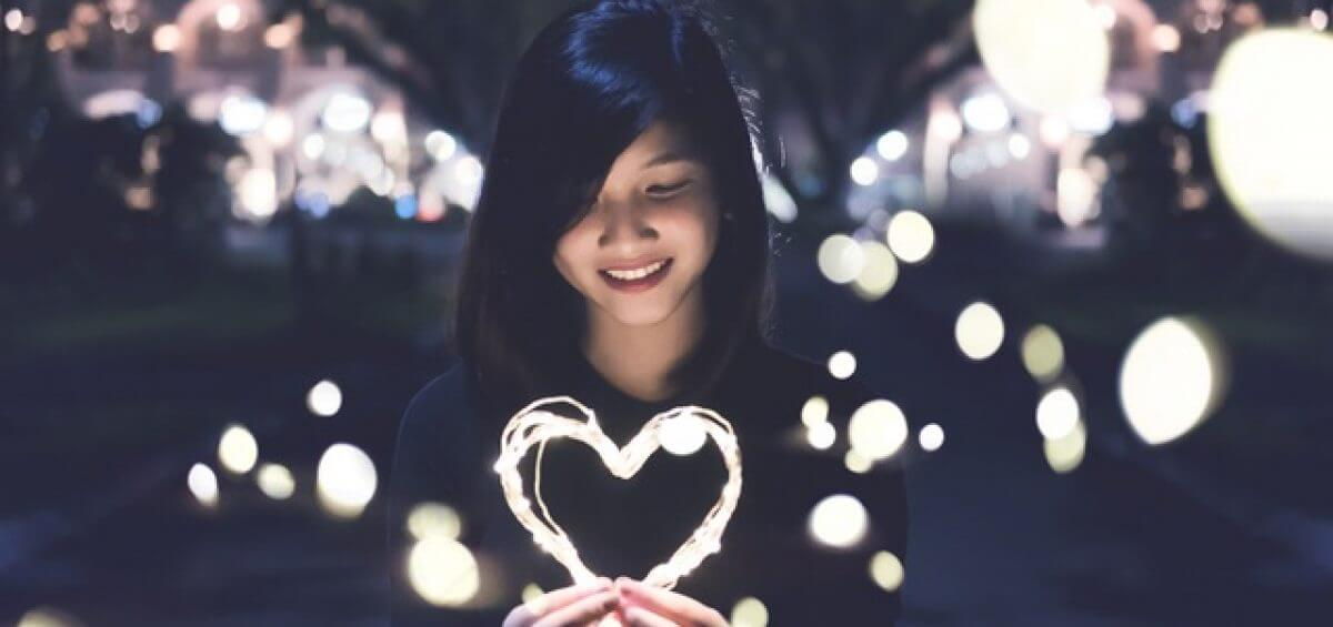 Young Asian woman holding string lights in the shape of a heart for the Perth international arts festival