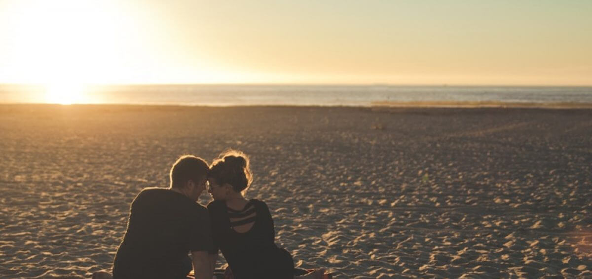 In love couple sitting on beach as the sunsets