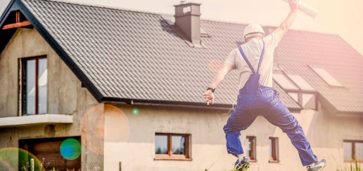 Builder jumping for joy with blueprint plans in his hand