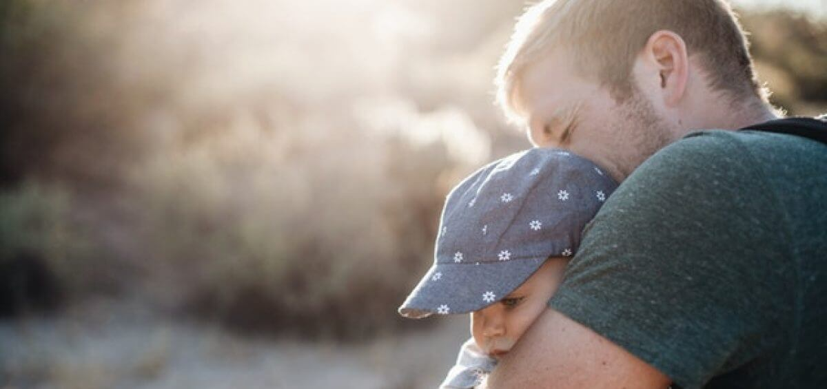Young father hugging his child, happy about permanent residence in Australia