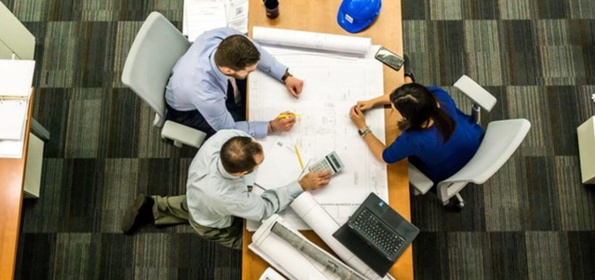 People sitting at business table discussing floor plans