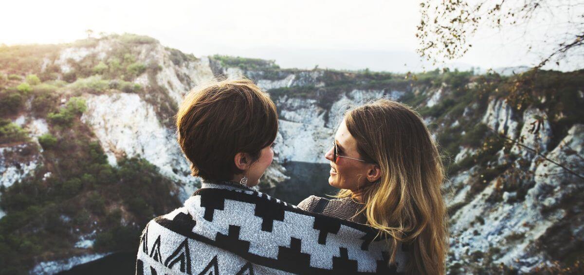 A same sex couple sitting on mountains