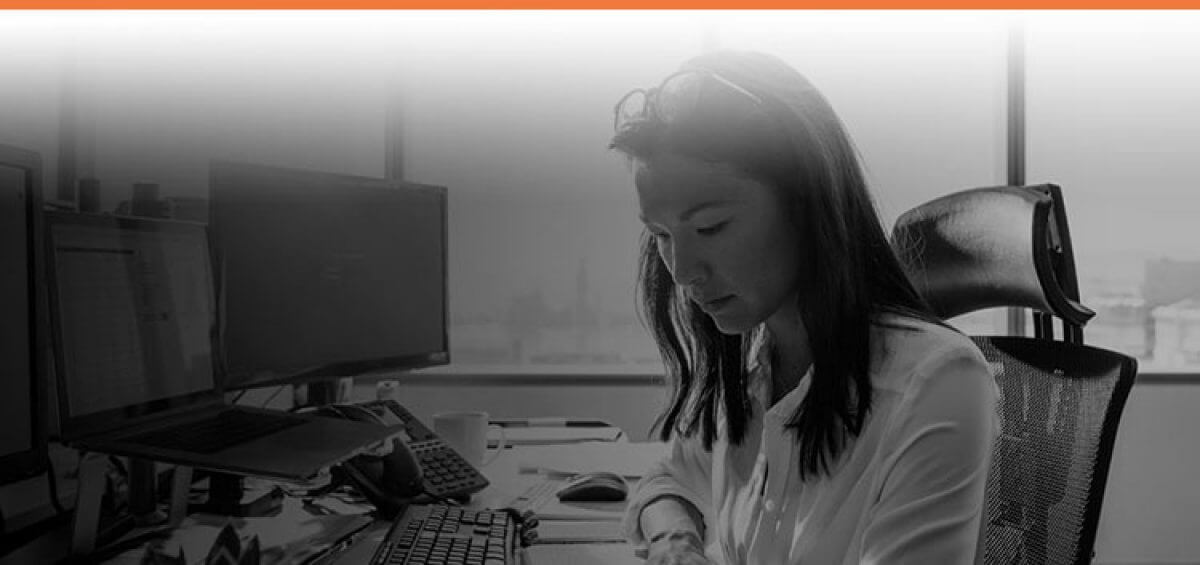 Woman doing work at her desk with Interstaff orange top border for Complex Migration service
