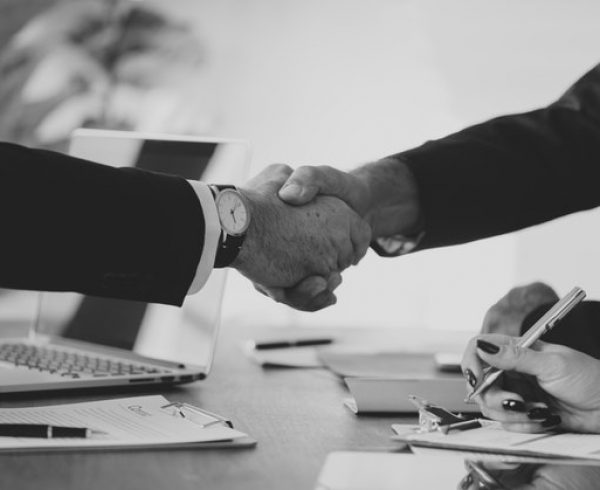 Two businesses shaking hands over a deal