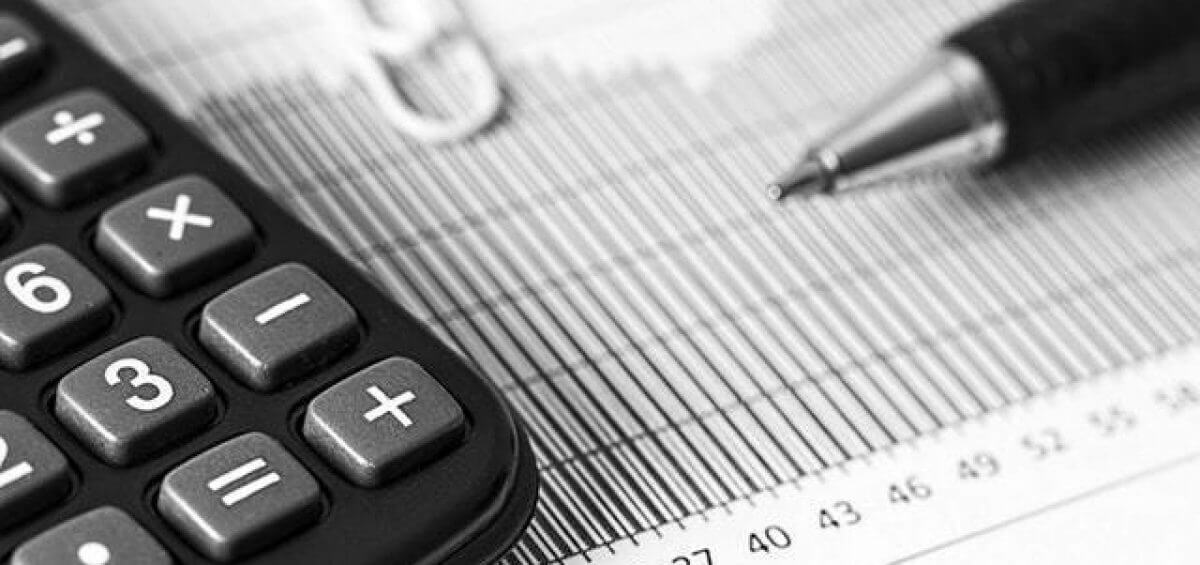 Closeup of a calculator and pen placed on top of a report as SAF refunds are calculated