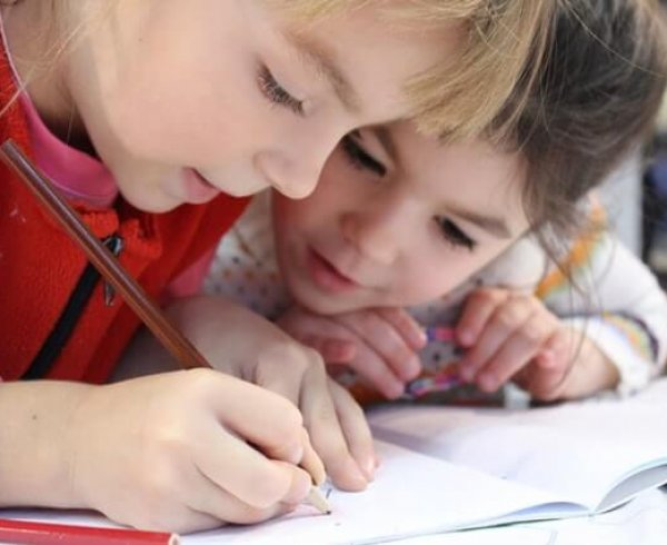 Two young girls doing a pencil drawing at school