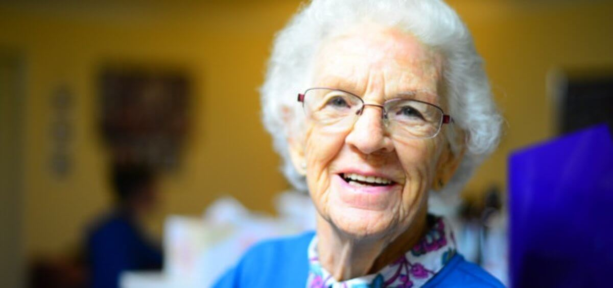 A happy elderly woman smiling over election promises for cheaper and more accessible parent visas
