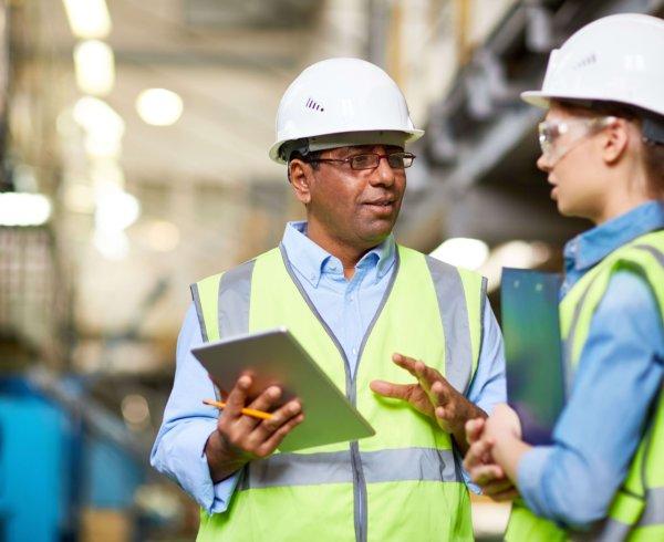 Two high-vis inspectors doing through checklist of work activities