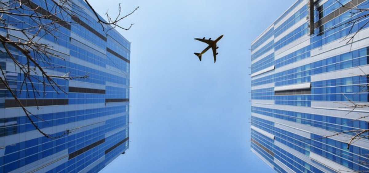 A plane flying over buildings for Visa Entry Conditions 8504