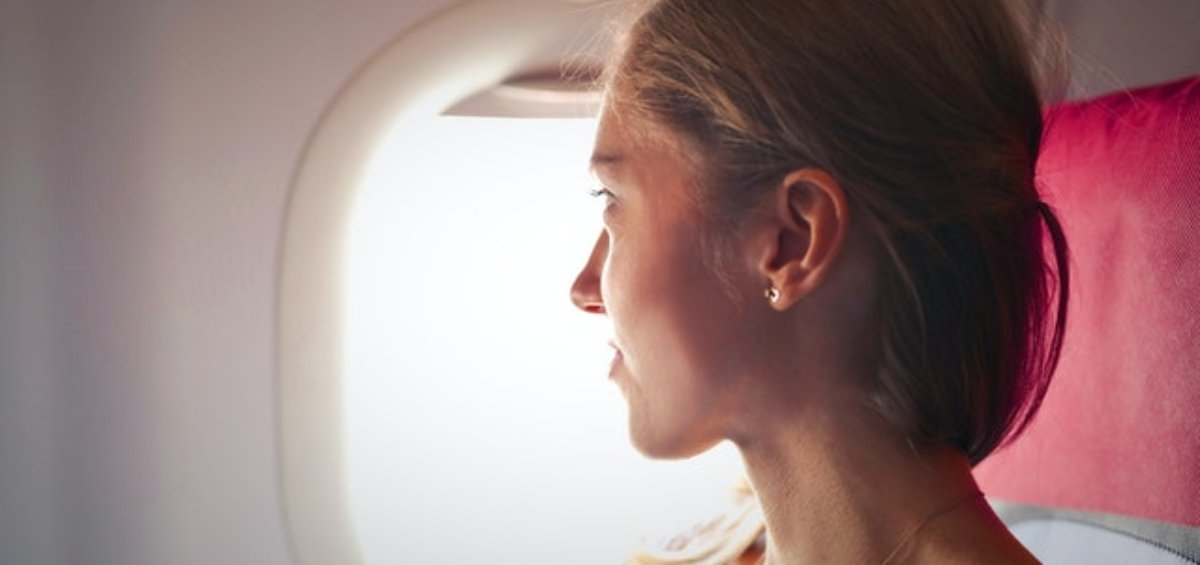 Woman looking outside of airplane as she reflects on temporary visa holder changes announced by the Government