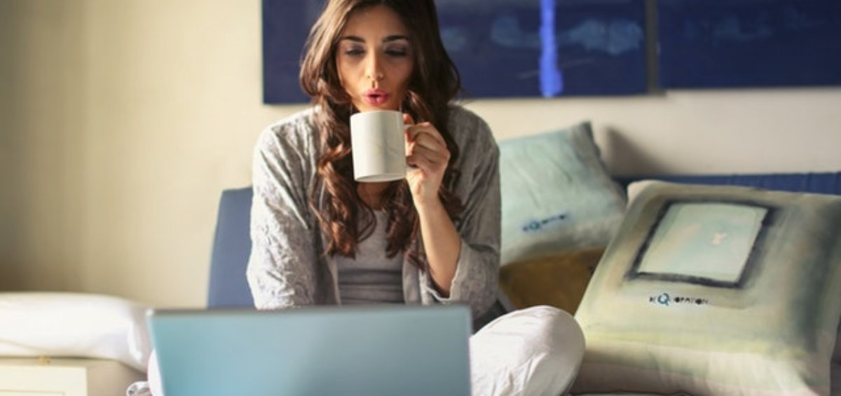Woman sitting in PJs on her bed searching online temporary visas in Australia