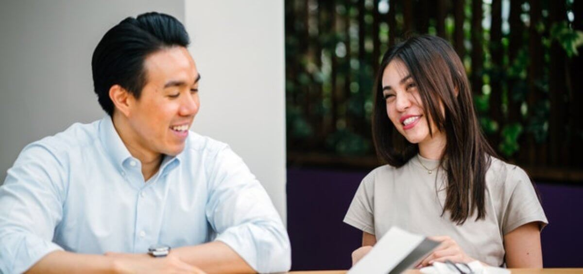 Couple sitting at desk discussing the Australia Government extending visa and PR options for Hong Kong Citizens in Australia